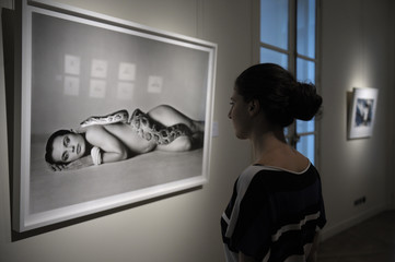 A visitor looks at the picture 'Nastassja Kinski and the Serpent, June 14, 1981' by photographer Richard Avedon displayed at Christie's auction house in Paris