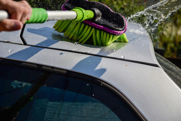 Young men washing silver car with pressured water and brush at sunny day. Close up of cleaning car on summer time. Taking care of the car. Man cleaning modern car with clear water in the garden