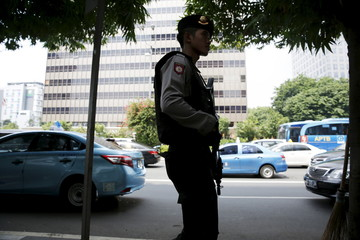 An Indonesian policeman holds a rifle as he patrols near a bomb blast site at the Thamrin business district in Jakarta