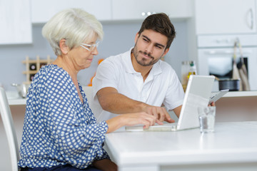 Young man showing elderly lady how to use laptop