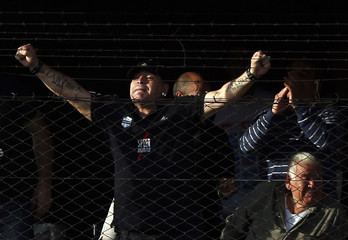 Former Argentina captain and coach Maradona celebrates behind a fence, next to his father, a goal by Deportivo Riestra during their Primera D championship soccer match against San Miguel in Buenos Aires
