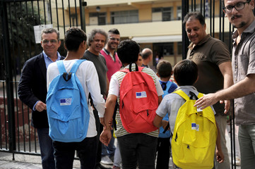 Refugee children enter a primary school on the first day of lessons under the new refugee schooling program, in Athens