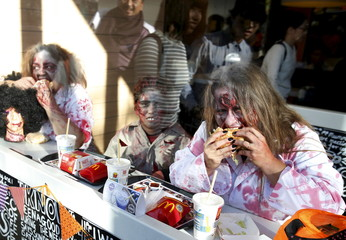 Participants in costume eat hamburgers inside a fast food restaurant after a Halloween parade in Kawasaki