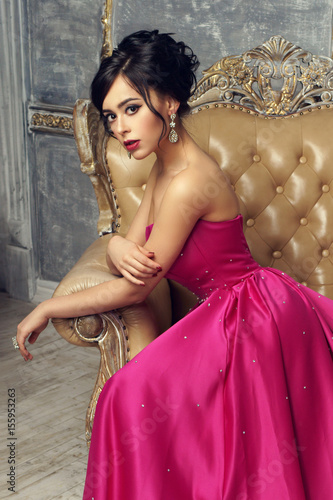 Elegant srunning woman sitting in armchair and looking at you ...