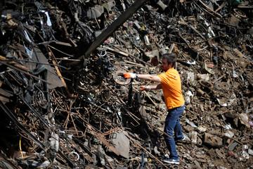 Jordanian graphic designer Abdelrahman Asfour, who turns car parts into furniture, looks through car parts at junkyard in Amman