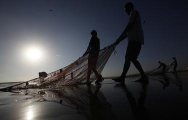 Fishermen pull their net while retrieving their catch at Karachi's Clifton beach