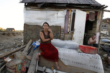 An ethnic Roma woman sits in front of her house in Craica slum at Romania's northern town of Baia Mare