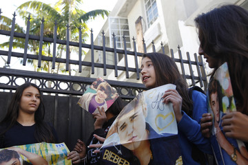 Some of the performer's  fans hold up images of Justin Bieber in the alley behind the hotel where the teen pop star is presumed to be staying in Miami Beach, Florida