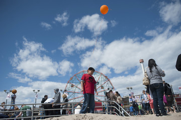 People make their way along the boardwalk in Coney Island in the Brooklyn Borough of New York
