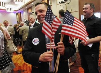A McConnell campaign volunteer hands out American Flags to campaign supporters for U.S. Senate Republican Leader Sen. Mitch McConnell  as they wait for elections results at Senator election night party in Louisville
