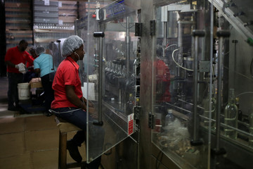 Woman watches as bottles are filled with Falernum liqueur at the Foursquare Rum Distillery in St. Philip, Barbados