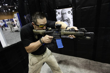 An exhibitor fires a dummy AR-15 style assault weapon at the seventh annual Border Security Expo in Phoenix