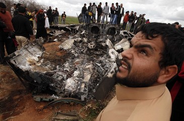 People look at a U.S Air Force F-15E fighter jet after it was crashed near the eastern city of Benghazi