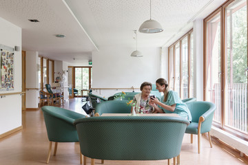 Nurse and senior woman sitting on couch in nursing home looking at pictures on smart phone