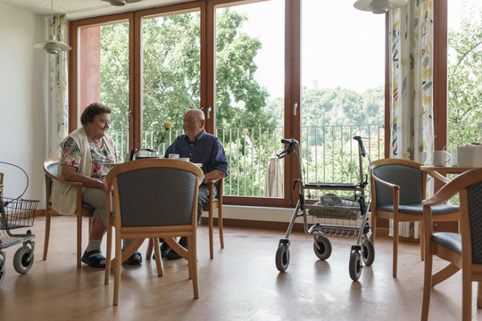 Senior man and woman sitting in cafeteria of rest home in the afternoon
