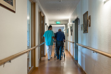 Nurse helping senior man with walking frame to get to his room in retirement home