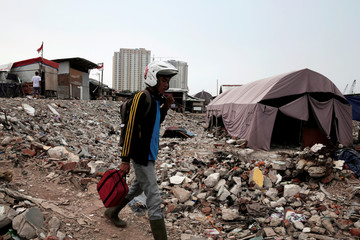 A man walks near a temporary shelter for people whose homes were demolished during eviction by the city authorities at Luar Batang district in Jakarta