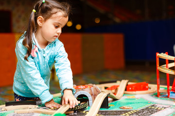 Joyful girl playing with toy railway
