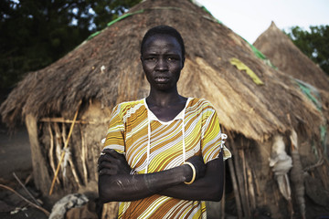 A Sudanese woman with ethnic Nuer tribal scarification stands outside her grass hut in Malakal