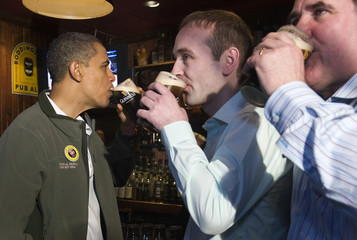 Obama drinks a pint of Guinness as he celebrates St. Patrick's Day with Healy and Hayes during a stop at the Dubliner pub in Washington