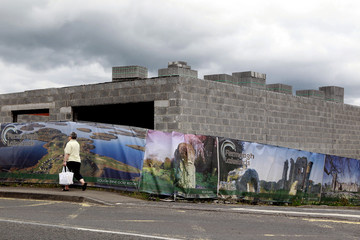 Security fencing covered with scenic pictures of County Fermanagh surrounds an unfinished building site in the village of Irvinestown