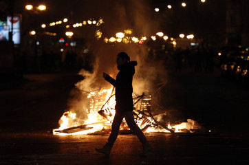 A woman passes by a fire set up in the middle of the road by protesters at the University Square in Bucharest