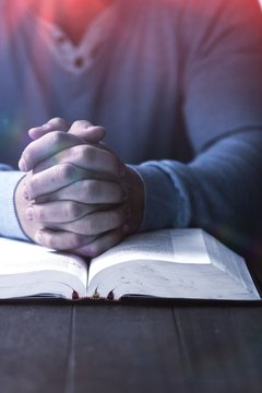 Mid section of man with bible praying