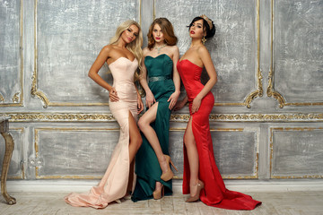 Three gorgeous stunning girls in mermaid evening dresses standing and posing in luxury interior. Brunette, blonde and red hair young elegant woman. Wall mural