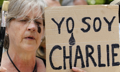 Woman, who has a painted tear near one of her eyes, holds a sign and a brush to pay tribute to the victims of the shootings at offices of satirical weekly newspaper Charlie Hebdo and a kosher supermarket, in Buenos Aires