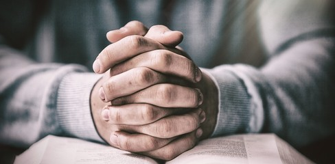 Close up of man with bible praying