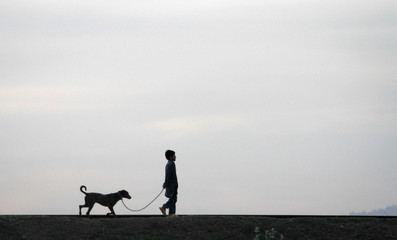 A boy is silhouetted as he walks with his dog on a railway track on the outskirts of Islamabad