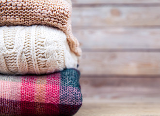 stack of clothes from knitted knitwear on a wooden background