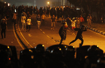 Protesters throw stones at the police during a clash outside the parliament building in Jakarta