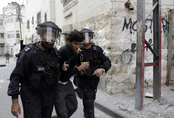 Israeli police officers detain a Palestinian suspected of throwing stones during clashes in the East Jerusalem
