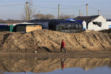"""A migrant walks past of a pile of sand which separates the road that leads to the ferry terminal and the camp known as the """"Jungle"""", a squalid sprawling camp in Calais"""