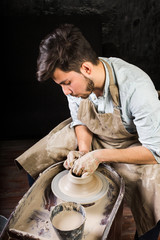 potter, workshop, ceramics art concept - closeup on working potter's wheel with raw clay and man's hands, young brunette male sculpt a utensil with fingers, master in apron, Mexican, Hispanic, Latino