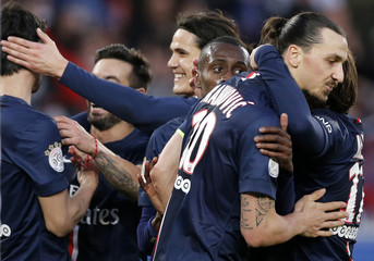 Paris St Germain players celebrate after Pastore scored the fourth goal for the team during their French Ligue 1 soccer match against RC Lens at Parc des Princes stadium in Paris