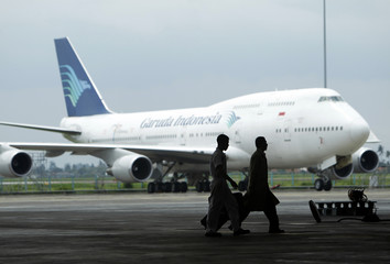 GMF AeroAsia technicians walk past a Garuda Indonesia aircraft on the tarmac at GMF AeroAsia's hangar in Tangerang