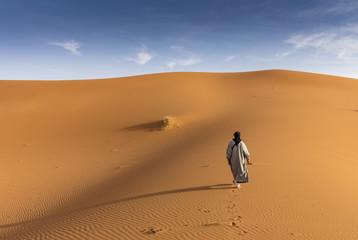 Berber man walking on the sand dunes of Erg Chebby, Merzouga, Morocco