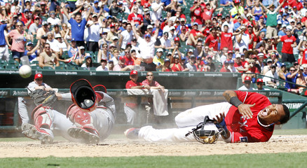 Texas Rangers Engel Beltre reacts after a scoring on a collision at home with Cincinnati Reds Devin Mesoraco in Arlington, Texas