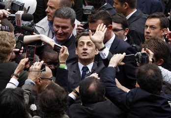 France's President and UMP party candidate for the 2012 French presidential elections Nicolas Sarkozy waves at a voting station after casting his ballot during the second round of 2012 French presidential election at a polling station in Paris