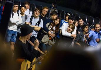 People listen to street musician in nightlife district of Hongdae in Seoul