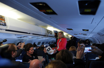 Ann, wife of Republican presidential nominee Romney, passes out pastries to reporters on the campaign plane before departing Newington