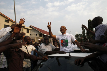 Michel Gbagbo waves from a car as he arrives at the headquarters of FPI in Abidjan