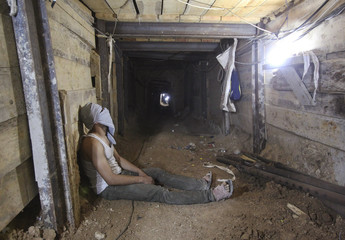 A tunnel worker rests inside a smuggling tunnel dug beneath the Gaza-Egypt border in the southern Gaza Strip
