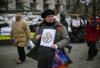 A pro-Russia protester holds an anti-swastika sign in front of a barricade outside a regional government building in Donetsk