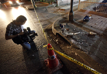 A cameraman films the site of an explosion outside a branch of the Bangkok Bank in Bangkok