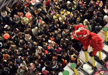 Worshippers look at a lion dance performance during the annual pilgrimage in honour of sea goddess Matsu in Dajia city
