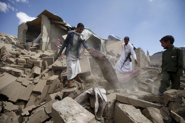 People salvage furniture from the rubble of a house destroyed by a Saudi-led air strike in Yemen's capital Sanaa