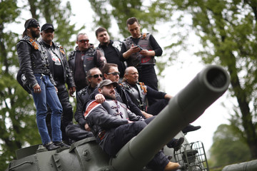 Members of the motorcycle group called Night Wolves coming from Russia, Macedonia and Bulgaria pose for a picture on top of a Red Army tank at the German-Russian museum Berlin-Karlshorst in Berlin